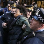 Lamon Reccord is taken into custody by Chicago police officers during a march calling for Chicago Mayor Rahm Emanuel and Cook County State's Attorney Anita Alvarez to resign in Chicago. Reccord was later released on the scene after protesters blocked the vehicle where he was being held.