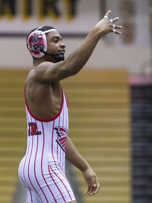 New Palestine High School's Chad Red celebrates his defeat of Warren Central High School's Tim Wright in the 132-pound weight class during the championship match of a IHSAA Sectional Wrestling Tournament at Shelbyville High School, Jan. 30, 2016.