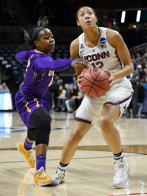 Albany's Imani Tate, left, reaches for the ball as Connecticut's Saniya Chong, right, looks up to the basket during the first half of a first round round of a women's college basketball game in the NCAA Tournament, Saturday, March 18, 2017, in Storrs, Conn.
