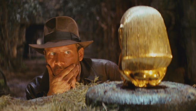 "Indiana Jones (Harrison Ford) sizes up an artifact in ""Raiders of the Lost Ark."""