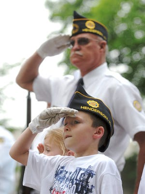 Michael Hanley, 7, salutes with his papaw Jim Hanley, rear, after the rifle volley at the Memorial Day service in Central Park in Henderson, Ky. Monday morning, May 25, 2009. Michael was determined to look like his grandfather and wore his old hat & gloves to the event. (Gleaner photo by Darrin Phegley • 831-8375 or dphegley@thegleaner.com)