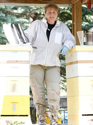 Denise Palkovich of Fond du Lac stands next to two of her honeybee hives. Wisconsin beekeepers are importing bees from as far away as California because of the high mortality rate of the insects in the state.