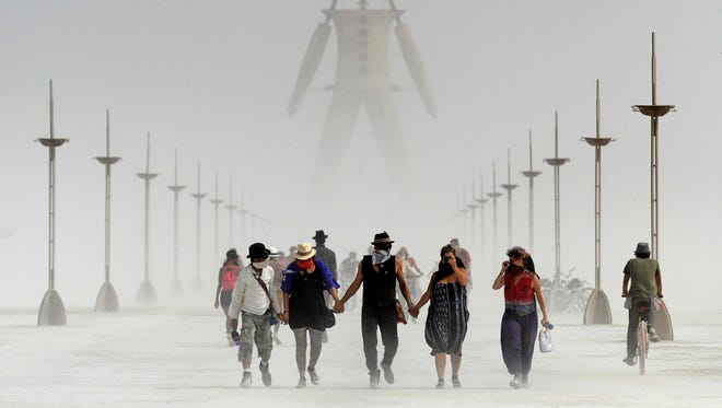 Burning Man participants walk during a dusty morning on the Black Rock Desert of Gerlach, Nev., on Aug. 29, 2014.