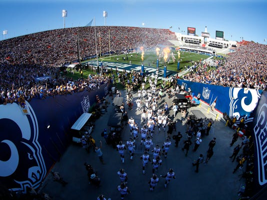 FILE - In this Aug. 13, 2016, file photo, The Los Angeles Rams take the field at Los Angeles Memorial Coliseum for a preseason NFL football game against the Dallas Cowboys in Los Angeles. The nation's second-largest city has waited nearly 22 years for Sunday. When the Rams take the field in a sold-out Coliseum for their first regular-season home game of the season, the NFL will truly, officially return to Los Angeles. (AP Photo/Ryan Kang, File)