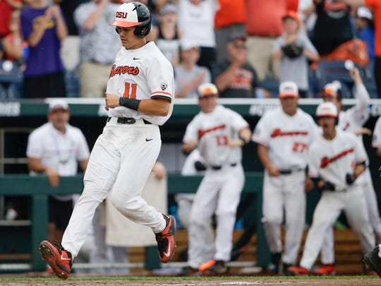 Oregon State designated hitter Trevor Larnach (11) scores the go-ahead run on a one-run single by Adley Rutschman against Cal State Fullerton in the eighth inning of an NCAA men's College World Series baseball game in Omaha, Nebraska in 2017. (AP Photo/Nati Harnik)