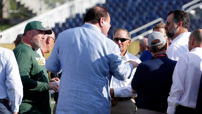Green Bay Packers coach Mike McCarthy, left, and Indianapolis Colts general manager Ryan Grigson, right, express their concern to David Baker, President/Executive Director of The Pro Football Hall of Fame, with the condition of the field before Sunday's NFL preseason game in Canton, Ohio.