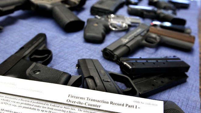A federal firearms transaction record, which includes a background check, lies near a selection of guns at Ron's Pawn and Gun in Des Moines.