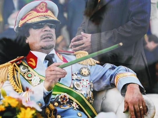 Libyan leader Moammar Gadhafi gestures with a green