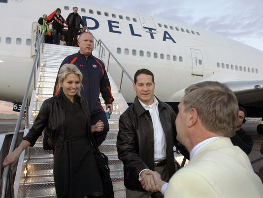 FILE - In this Jan. 3, 2011, file photo, Auburn coach Gene Chizik, center, is greeted by BCS championship game ambassador Duane Woods, right, at Sky Harbor International Airport  in Phoenix as Chizik's wife, Jonna, watches After two years of living and working in Chapel Hill, N.C., while his wife and three children were in Auburn, Ala., Chizik has quit his job and returned home to be a full-time dad and husband. The lengthy long-distance relationship he had with his family is not uncommon among college football coaches as they job hop through a career with little security. (AP Photo/Paul Connors, File)