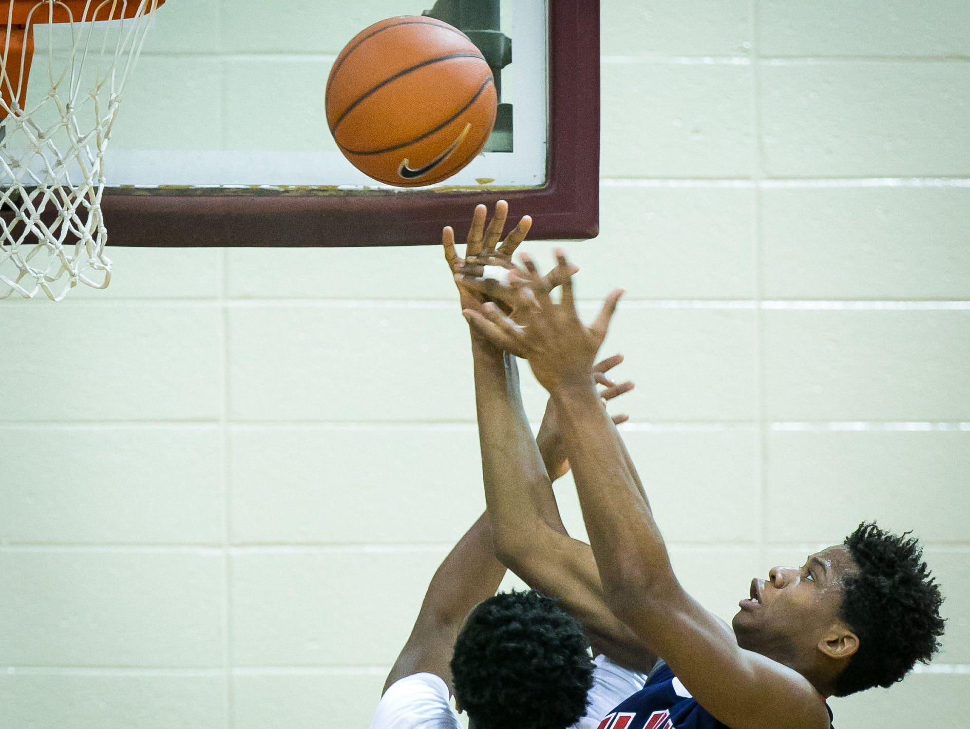 Yvens Monfluery (right) of American History gets fouled by Richard Caldwell of Mount Pleasant as he drives to the basket.