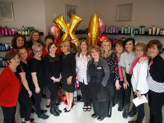 Maureen Freebery stands with her longtime staff at her business, Maureen's Hair Salon & Day Spa, which is celebrating its 50th year.