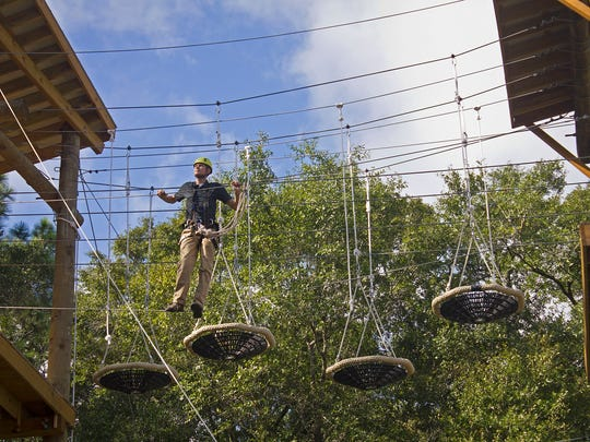 "FSU Campus Recreation staff member Travis Johnson maneuvers through the High Challenge Course obstacle known as ""Basket Case"" at the FSU Reservation on Monday. The Challenge Course has a grand opening Thursday at 3 p.m."