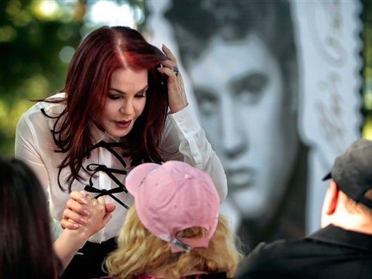 En la imagen, Priscilla Presley saluda a seguidores de Elvis Dawn and Phillip Pratt tras una presentación del nuevo sello de Elvis Forever, el segundo sello postal el icono de la música, el miércoles 12 de agosto de 2015 en Memphis. (Jim Weber/The Commercial Appeal via AP)