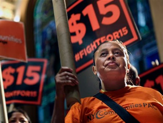 In this June 15, 2015, file photo, demonstrators rally for a $15 minimum wage before a meeting of the state Wage Board in New York. The New York state Wage Board is expected to recommend a higher minimum wage for the industry during a meeting, Wednesday, July 22, 2015, in New York City. Board members say they support an increase, though they haven t offered a specific amount.