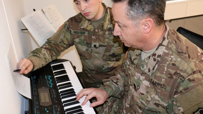 FORT CAMPBELL, Ky.— Spc. Walter Reuter, a pianist with the 101st Airborne Division (Air Assault) Band, helps Lt. Col. Arnaldo Huertas, a Soldier with the Fort Campbell Warrior Transition Battalion, play through a challenging section of a song during a music lesson Feb. 1. The battalion's Occupational Therapy department partners with the 101st Airborne Division (Air Assault) Band to provide musical instruction to Soldiers at the WTB. Playing a musical instrument helps Soldiers improve hand-eye coordination and manual dexterity, improves concentration and helps regulate mood. U.S. Army photo by Maria Yager.