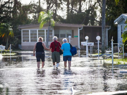 Larry Donnerstag, 87, center, is helped back to his home at Naples Estates trailer park in East Naples Monday, Sept. 11, 2017, after Hurricane Irma passed through southwest Florida.