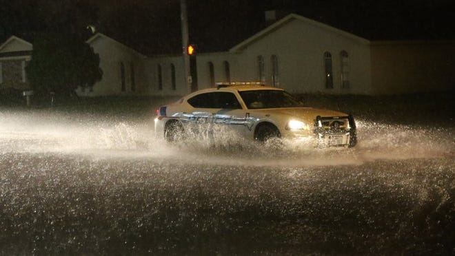 Yfat Yossifor / Standard-Times San Angelo Police crosses an intersection flooding with water as the storm rolls in.