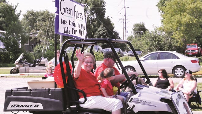 Parade participants wave to the crowd at the Sacred Heart Parish Festival in Freeport in 2014.
