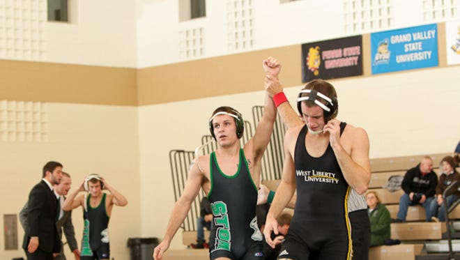 Thomas McVicker raises his arm in victory after pinning his opponent during a collegiate match for Lake Erie College in 2011. McVicker was named Lely's wrestling coach Monday.