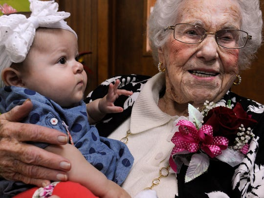 Ferne Lee holds her Clara Canada during Lee's party celebrating her 100th birthday. Lee is the great-great-great aunt to the 8-month-old baby.