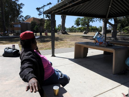 A woman hangs out in Sherwood Park on Thursday. Salinas is adding security patrols to Sherwood Park and on-call social workers to the Steinbeck Library to address safety concerns related to some of the homeless, officials say.