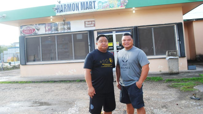 Brothers Sam and Dominic San Gil, youngest of the 10 San Gil siblings born to the late Roberto C. San Gil and Dolores San Nicolas San Gil, stand in front of the store that sustained their family since 1973. Harmon Mart will close its doors for good Dec. 29.
