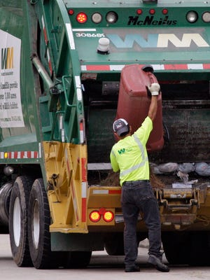 Waste Management workers pick up trash in a Spring, Texas neighborhood. .