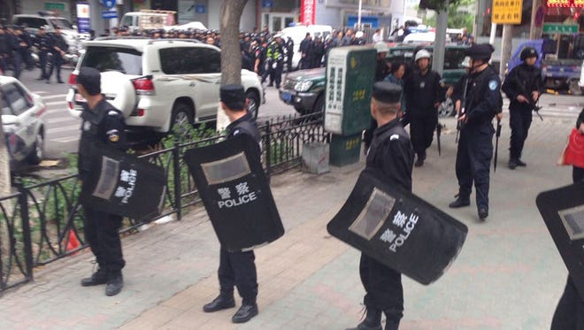 In this photo released by China's Xinhua News Agency, police officers stand guard near a blast site which has been cordoned off, in downtown Urumqi, capital of northwest China's Xinjiang Uygur Autonomous Region, Thursday.