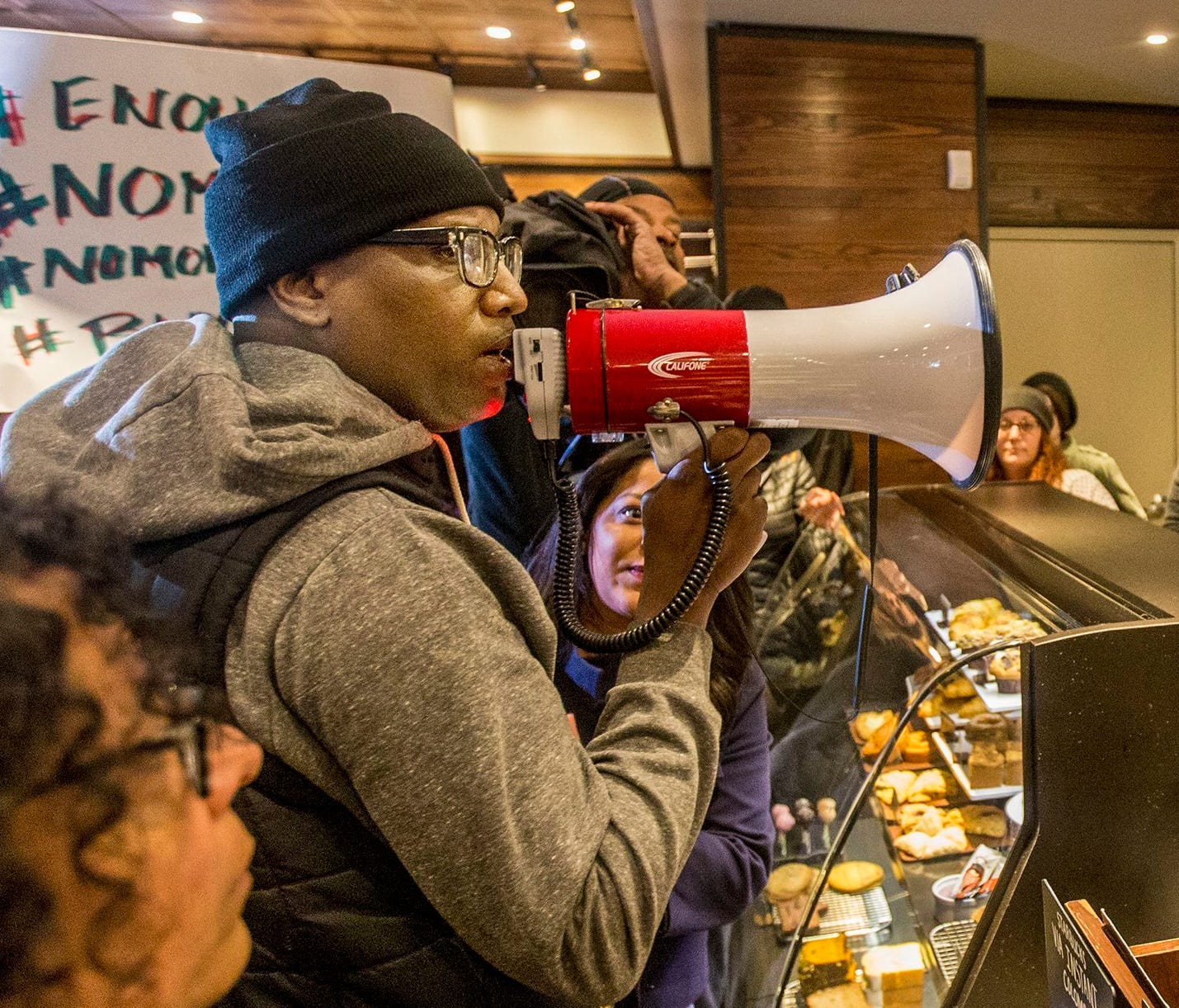 Local Black Lives Matter activist Asa Khalif, left, stands inside a Starbucks, April 15, 2018, demanding the firing of the manager who called police resulting in the arrest of two black men on Thursday. The arrests were captured on video that quickly