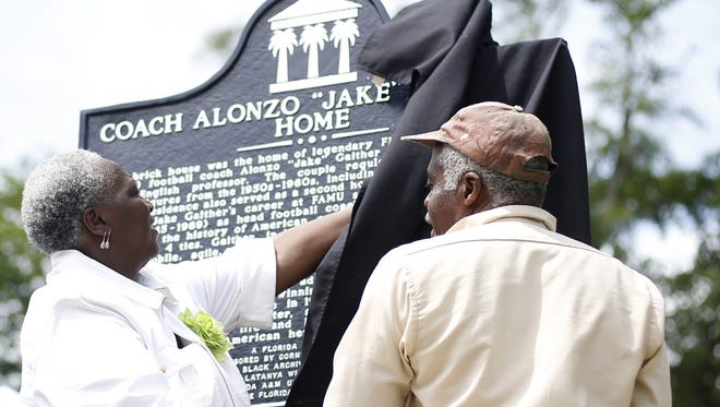"""Dr. E. Murrell Dawson, left, and Edison Bruce unveil the marker for Coach Alonzo """"Jake"""" Gaither, famed FAMU football coach, on Friday at 212 Young Street where he lived while coaching the Rattlers."""