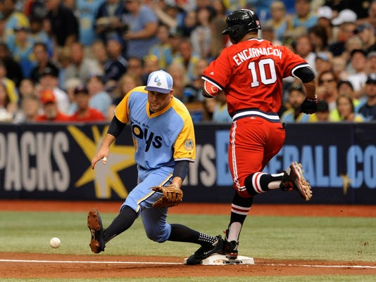 Cleveland Indians' Edwin Encarnacio (10) beats the throw to Tampa Bay Rays first baseman Lucas Duda, left, from third baseman Trevor Plouffe for an infield hit during the first inning of a baseball game Saturday, Aug. 12, 2017, in St. Petersburg, Fla. Both teams are wearing throwback jerseys. (AP Photo/Steve Nesius)