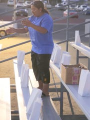 Event leader Mychelle McGee lights luminarias in the stands during Saturday's Relay for Life at the Boys & Girls Clubs of Farmington football field.