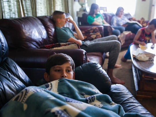 Elisha, 10, snuggles up for history lesson read by his mother, Deja Armstrong, Tuesday, April 3, 2018, in the living room at home.