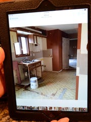 Drochak displays a photo on her tablet computer that shows how her kitchen looked at the beginning of the renovation.