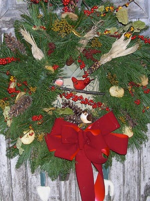 To make a bird watchers' wreath, start with a fresh  evergreen wreath and attach berries, seeds and other things that attract birds.