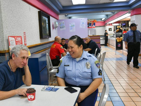 """Tamuning resident Patrick Sullivan, left, talks with Officer Susie Santos during Guam Police Department's Coffee with a Cop outreach at the Tamuning McDonald's on Jan. 25, 2017. Sullivan said he was glad to see police be in touch with the community, and that it was """"reminiscent of what Gov. (Ricky) Bordallo did years ago."""""""