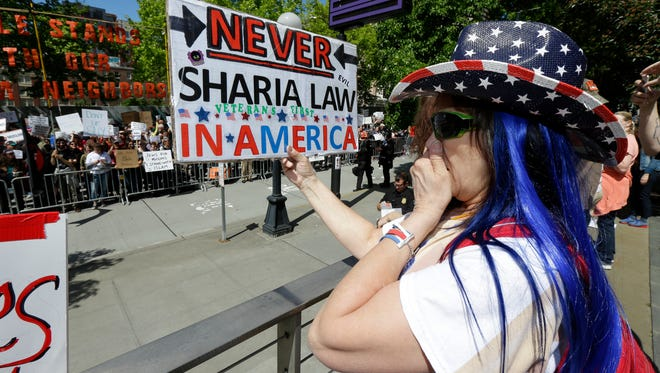 Cathy Camper, of Tacoma, Wash., wears a stars-and-stripes cowboy hat as she protests against Islamic law and reacts to counter-protesters across the street at a rally June 10, 2017, in Seattle.