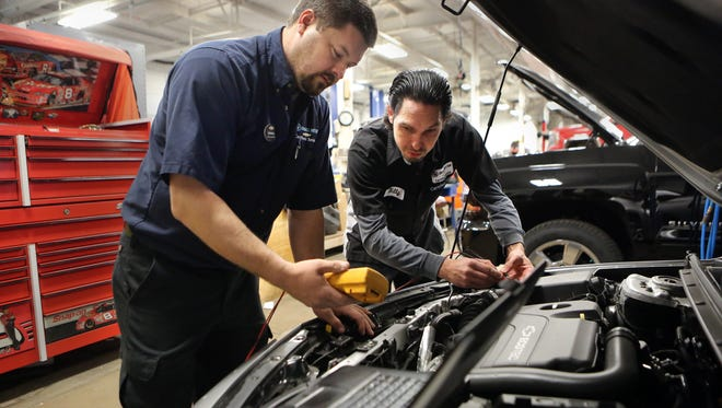 Shop Foreman Derrick Richter (left) and ASE Master Auto Technician Billy Hampton use diagnostic computer technology in the shop at Chuck Hutton Chevrolet. Memphis auto dealers and Moore Tech are setting up a car tech school.