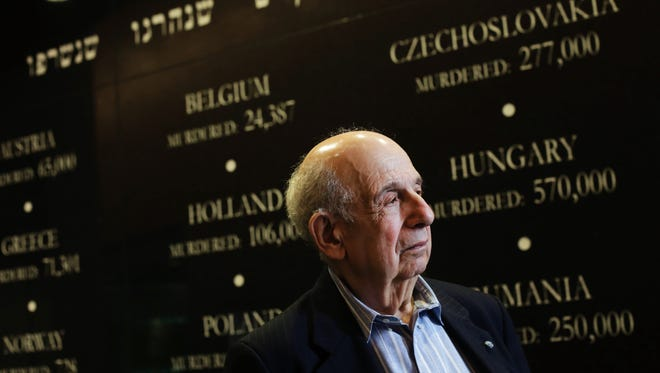Guy Stern, 92, works at the Holocaust Memorial Center in Farmington Hills, Mich., where a Wall of Remembrance shows how many Jews perished from European countries occupied by the Germans in World War II .