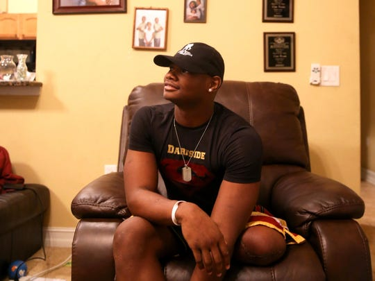 Cam Brown, who recently had his left leg amputated due to complications with osteosarcoma, an aggressive type of bone cancer, sits at his home amoungst family photos and athletic trophies he has won over the years.