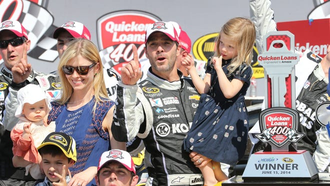 Jimmie Johnson holding his daughter Genevieve, stands with his wife Chandra Janway after winning the Quicken Loans 400 on Sunday at Michigan International Speedway in Brooklyn, Mich.