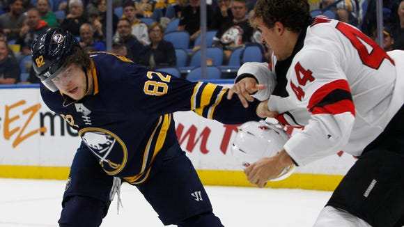 Buffalo Sabres Nathan Beaulieu (82) and New Jersey Devils miles Wood (44) fight during the second period of an NHL hockey game, Monday Oct. 9, 2017, in Buffalo, N.Y. (AP Photo/Jeffrey T. Barnes)