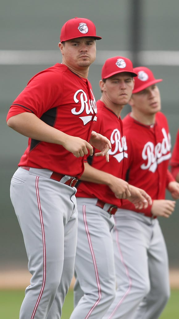 (From left:) Pitchers Nick Travieso, Anthony DeSclafani, Nick Howard and Robert Stephenson warm up at spring training.