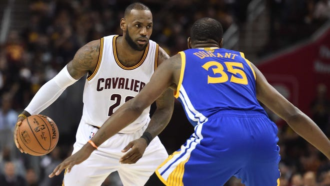 Cleveland Cavaliers forward LeBron James (23) works around the defense of Golden State Warriors forward Kevin Durant (35) during the third quarter in game three of the 2017 NBA Finals at Quicken Loans Arena.