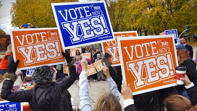 Supporters hold signs in support of the coming District 742 referendum during a rally Oct. 24, 2015 at Lake George in St. Cloud.