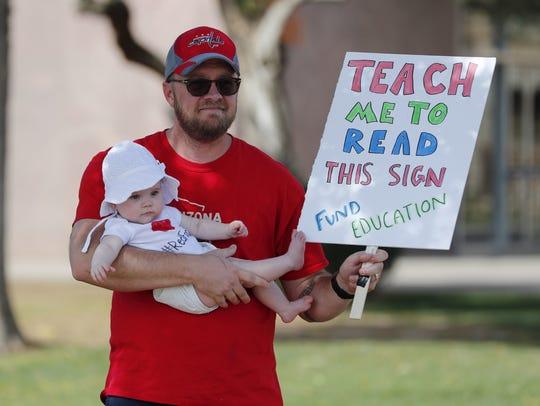 Jon Kreibich sostiene a su hija con una mano, y con