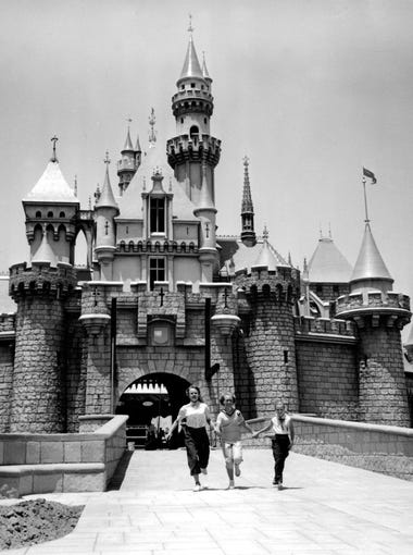 Three people walk hand-in-hand in front of a castle at Fantasyland in Disneyland in Anaheim, California on July 5, 1955. The park opened to visitors on July 17, 1955.