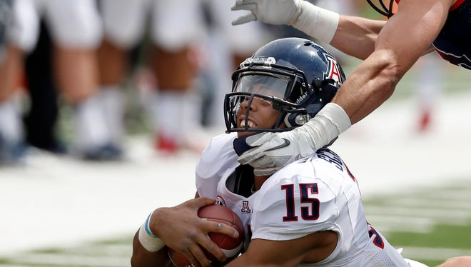 Arizona quarterback Jesse Scroggins gets dragged down by his neck by safety Brogan Kemmerly ending his run around the end at Arizona Stadium in their Spring Game, Friday, April 12, 2014.