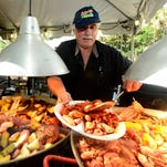 Robert Adams with Seafood Unlimited serves up a plate of crawfish for customer Jeremy Hall on Friday at Olde Seville Square on the opening day of the 38th annual Pensacola Seafood Festival. The festival continues on Saturday from 10 a.m. to 11 p.m. and Sunday from 11 a.m. to 5 p.m.