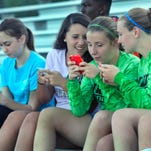 Webster Schroeder 10th-graders, from left, Cate Muir, Ashley Bonafede, Sarah Smagala and Samantha Neill tweet about their girls soccer team during a game last week.